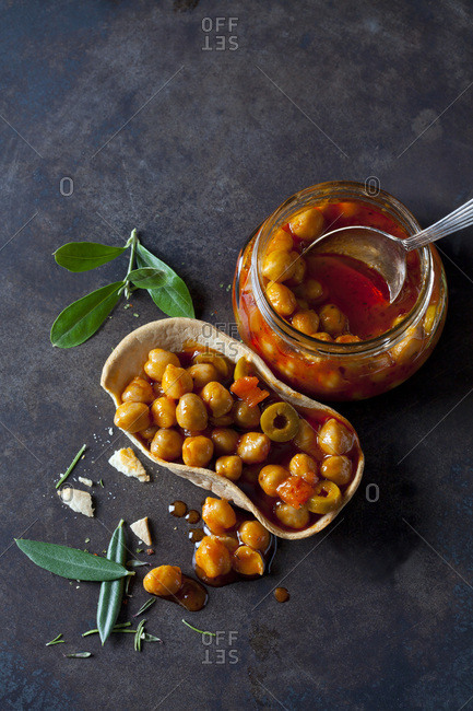 Chick-pea stew with green olives in glass and edible bowl