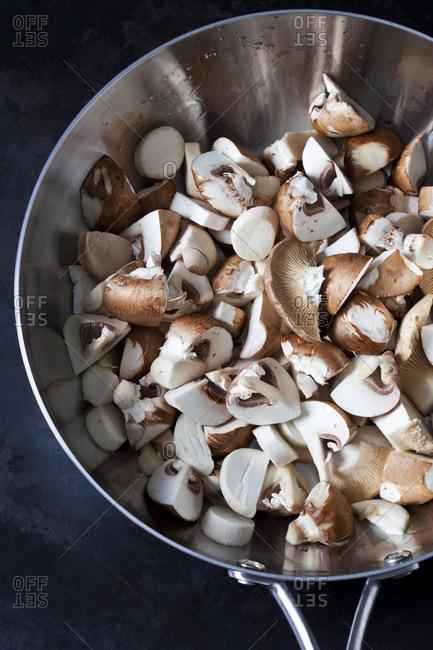Sliced Crimini Mushrooms in stainless steel pan