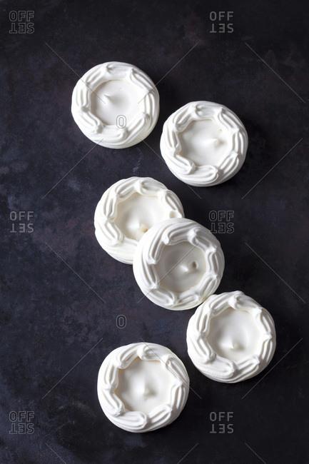 Six meringues on dark ground