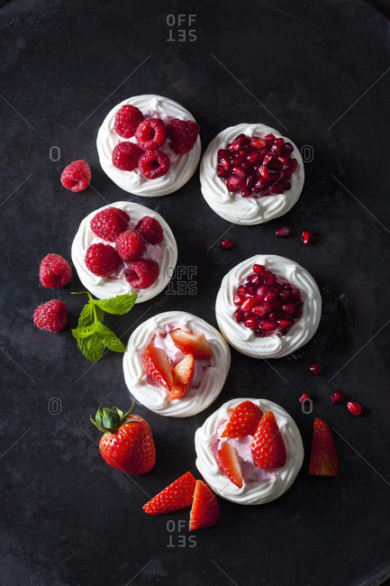 Meringue pastries garnished with whipped cream- berries and pomegranate seed