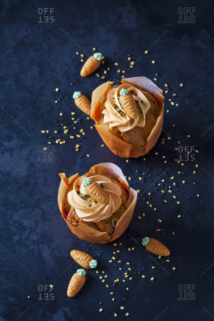 Two carrot cup cakes garnished with  cream topping- sugar granules and marzipan carrots