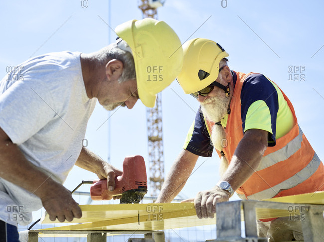Construction worker cutting plywood with jigsaw on construction site