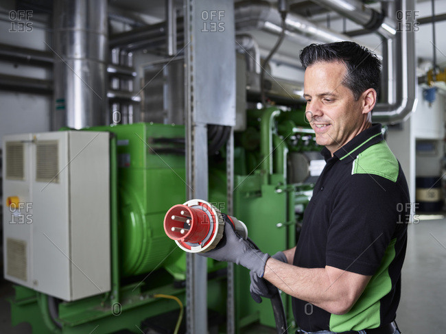 Combined heat and power plant- worker holding high current plug