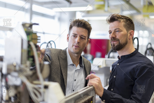 Two businessmen examining device in factory