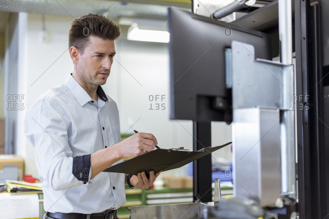Man with clipboard in factory looking at screen