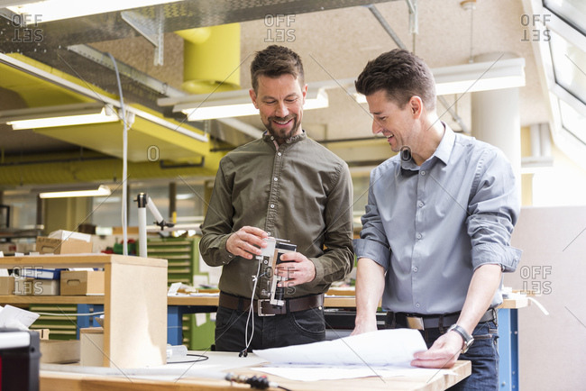 Two smiling men with plan looking at product in factory