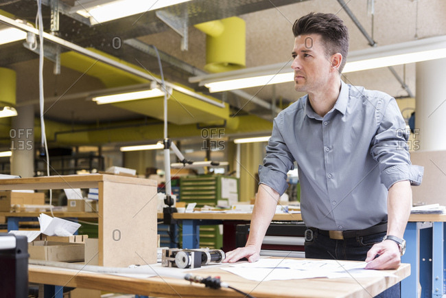 Man in factory with plan looking around