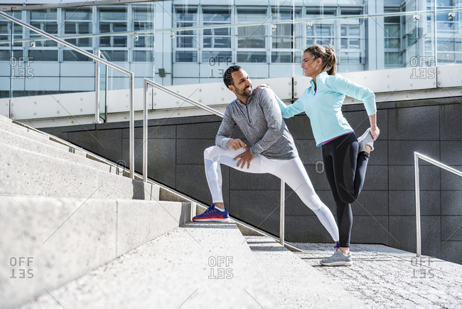 Couple doing stretching exercise on stairs in the city