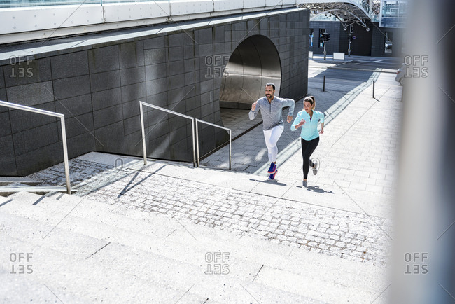 Couple running on stairs in the city