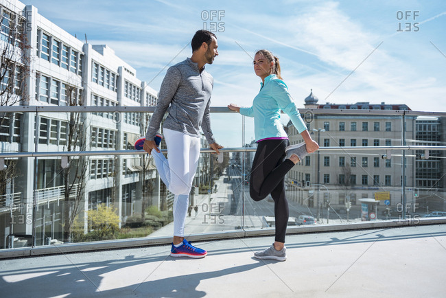 Couple doing stretching exercise on bridge in the city