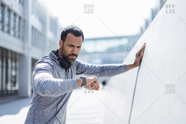Man having a break from exercising looking on smart watch