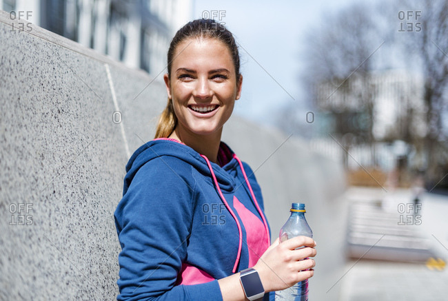 Smiling young woman having a break from exercising