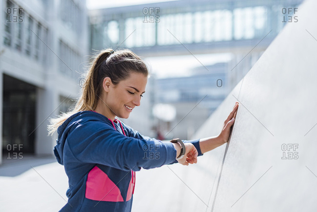 Smiling young woman having a break from exercising looking on smart watch