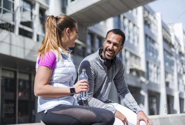Active couple with water bottle having a break in the city
