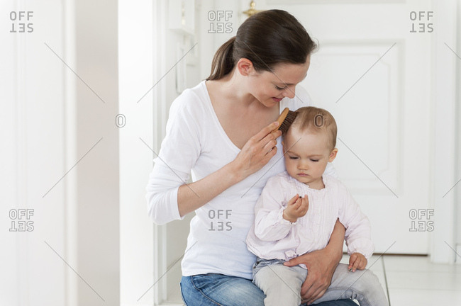 Mother brushing baby's hair at home
