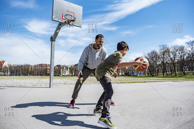 Father and son playing basketball on court outdoors