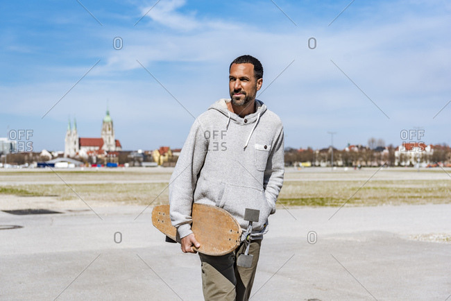 Man carrying longboard outdoors