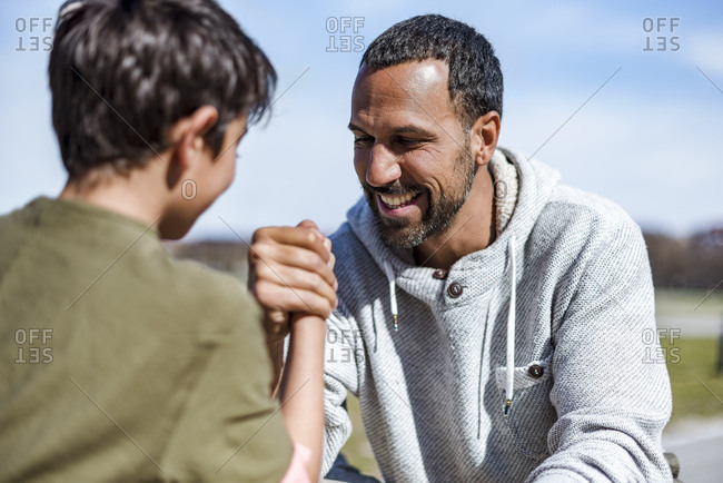 Father and son arm wrestling outdoors