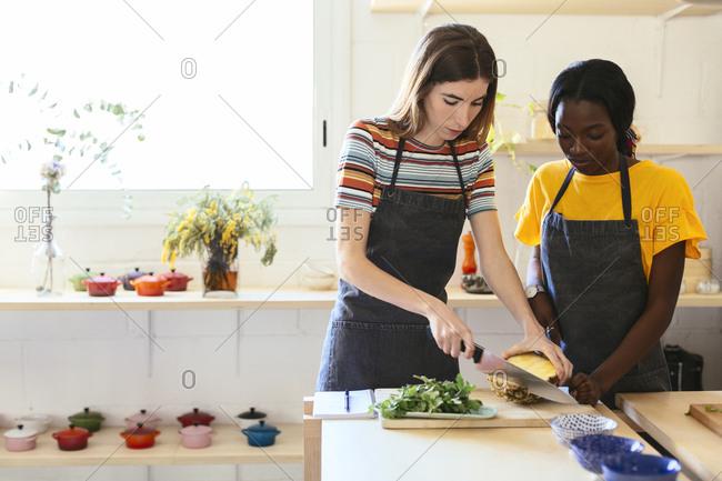 Friends preparing pineapple in kitchen