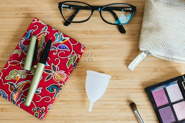 Menstrual cup on a table and notebook- pen and glasses