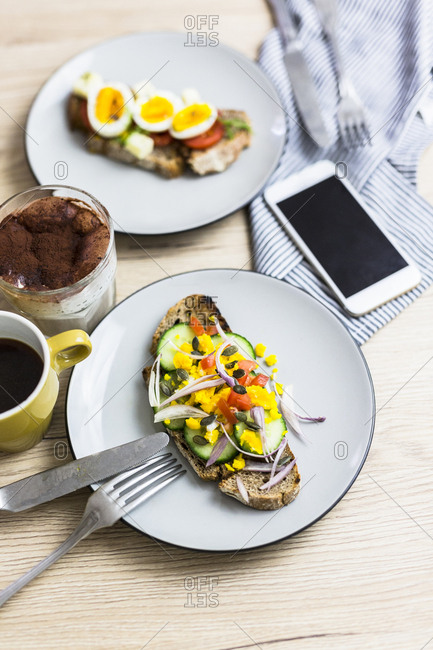 Vegetarian breakfast with bread- eggs and cucumber slices on plate- smartphone- latte macchiato- coffee cup