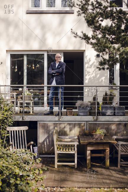 Senior man standing on his veranda- looking proud