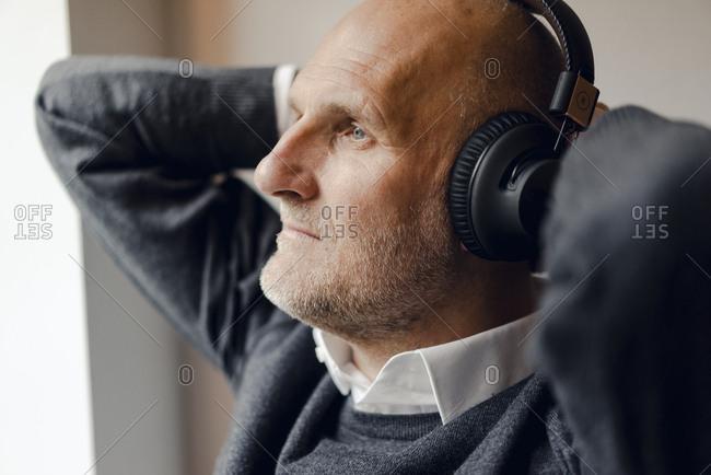 Senior man wearing headphones- listening music- portrait