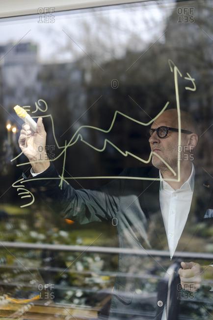 senior businessman brainstorming- drawing formulas on window pane