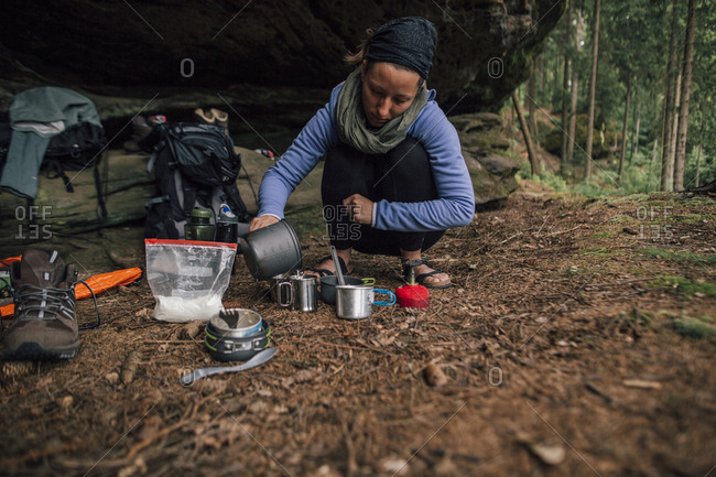Young woman on a trekking tour preparing drinks