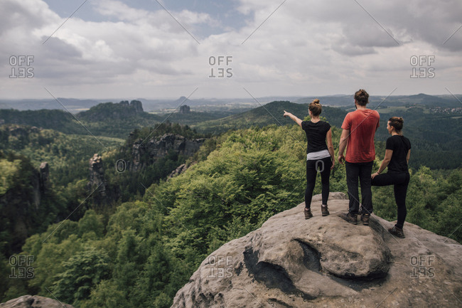 Germany- Saxony- Elbe Sandstone Mountains- friends on a hiking trip standing on rock