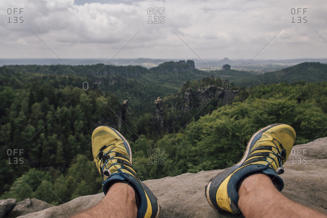 Germany- Saxony- Elbe Sandstone Mountains- man\'s feet on a hiking trip sitting on rock