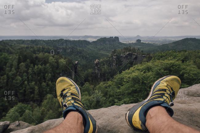 Germany- Saxony- Elbe Sandstone Mountains- man\'s feet on a hiking trip sitting on rock