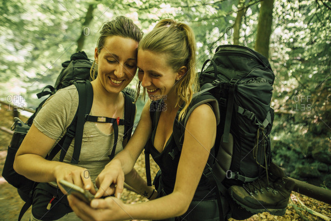 Two happy young women on a hiking trip using cell phone