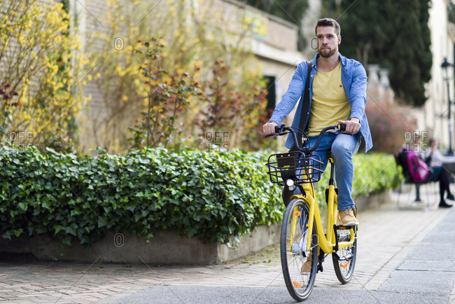 Young man riding rental bike in the city