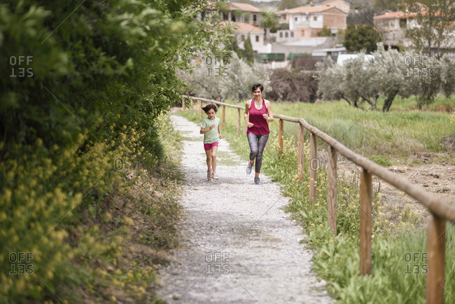 Mother and daughter running on a path in nature environment
