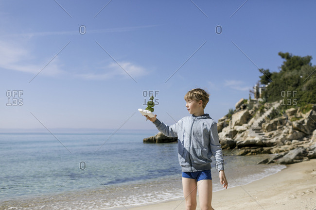 Boy standing on the beach with self-made toy boat