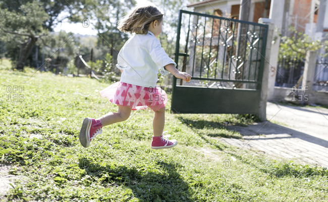 Little girl running on meadow in the garden