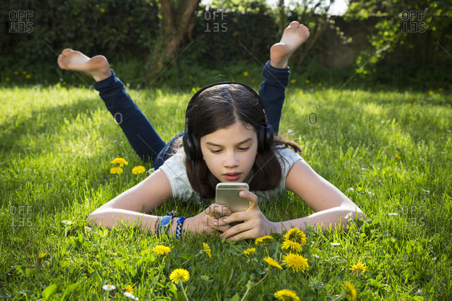 Girl lying on meadow listening music with headphones using smartphone