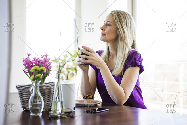 Mature woman sitting at table relaxing with glass of coffee