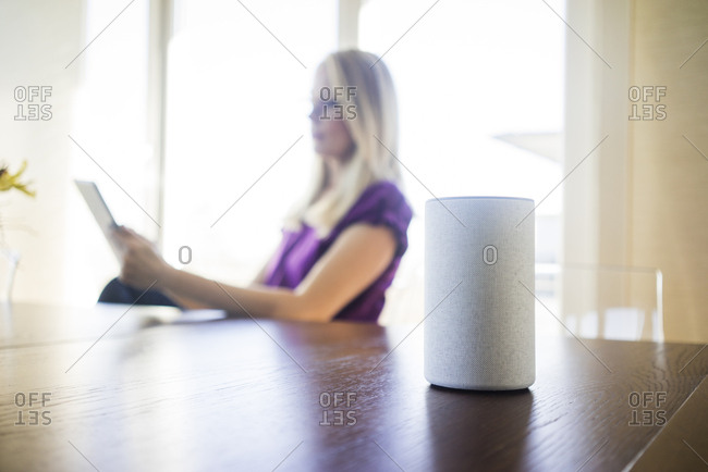 Smart Home loudspeaker on table with woman using tablet in the background