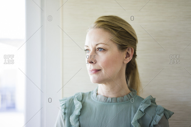 Portrait of blond mature woman looking out of window
