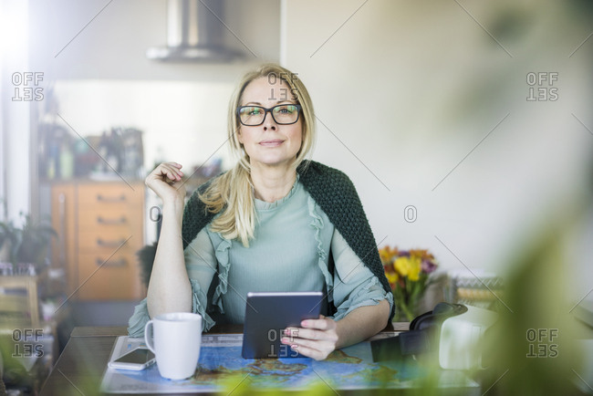 Portrait of blond businesswoman with tablet and world map