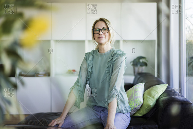 Portrait of content businesswoman sitting on couch