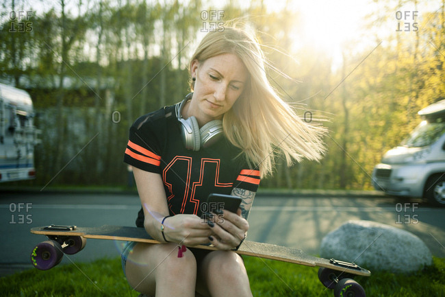 Portrait of blond woman with longboard sitting at roadside using smartphone
