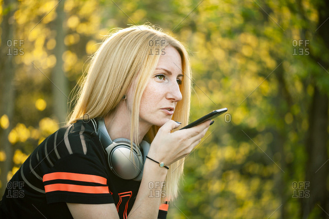 Portrait of blond woman with headphones using smartphone