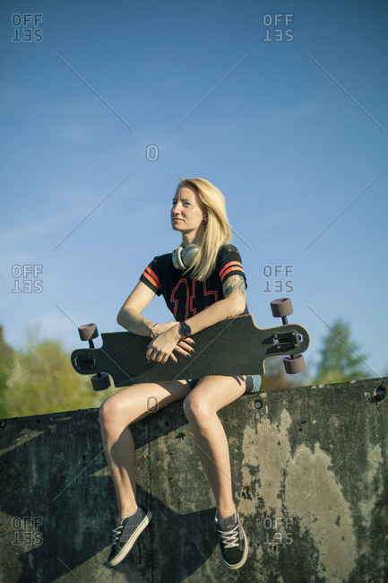 Blond woman with longboard sitting on wall at sunlight