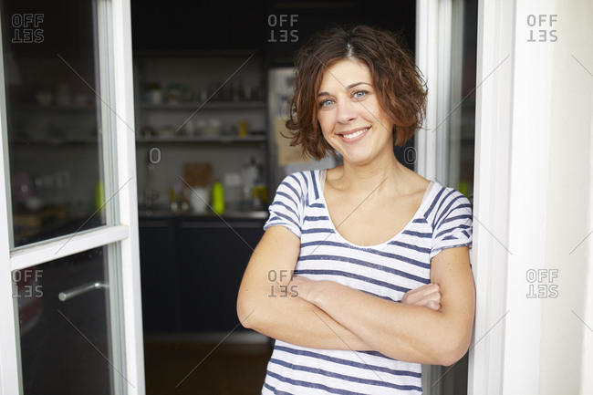 Portrait of content mature woman leaning against open balcony door