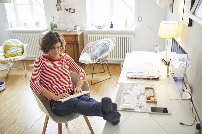 Mature woman sitting with feet up at desk at home using cordless keyboard