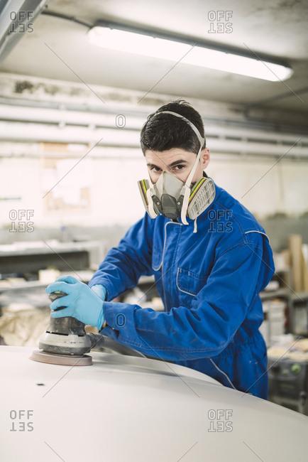 Portrait of man polishing the hood of a car in a workshop