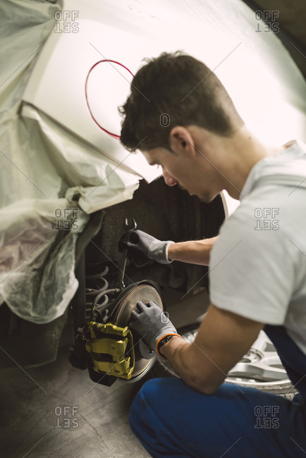 Mechanic fixing the brake caliper of a car in a workshop